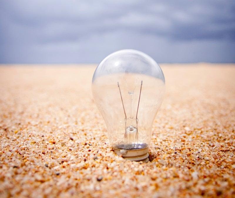 Unlit lightbulb sitting in sand